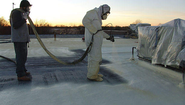 Spray foam application with tail hose man assisting