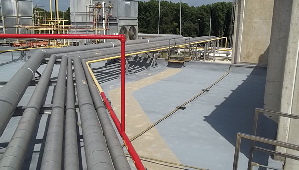 Dark grey industrial spray foam roof with raised pipes
