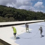Spray roofing application by Dura-Foam worker